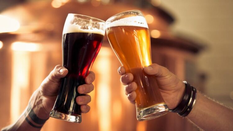 Image of hands toasting with glasses of craft beer in front of distillery vat.