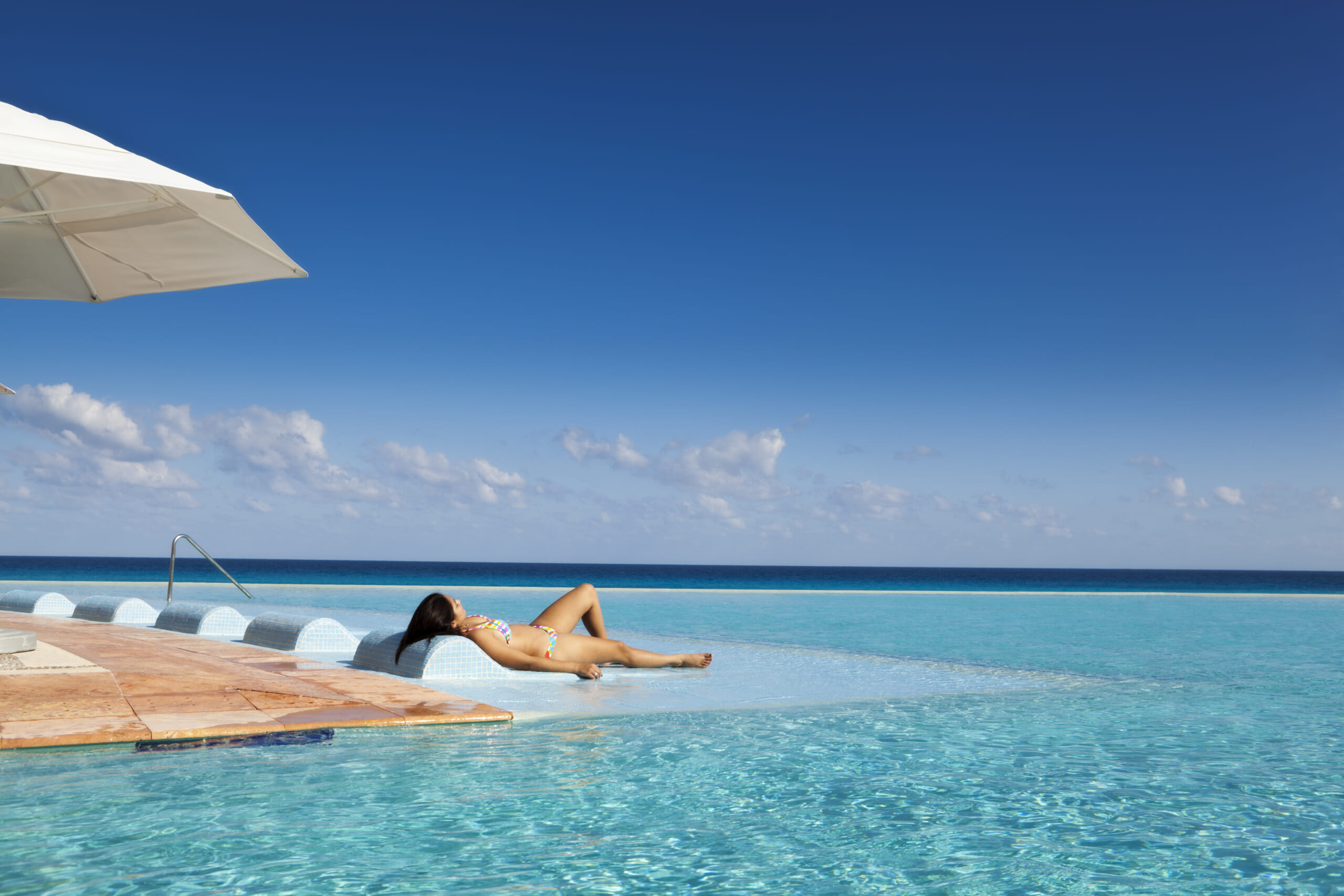 A young woman by a tropical beach resort hotel infinity pool on the Caribbean Sea, Cancun, Riviera Maya, Mexico.