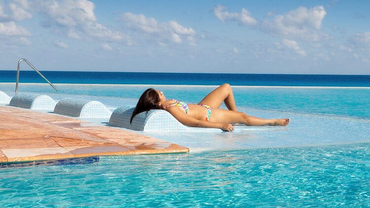 Detail from photo of a young woman by a tropical beach resort hotel infinity pool on the Caribbean Sea